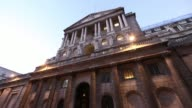 Various exterior shots of Bank of England at dusk city traffic and pedestrians passing by Bank of England exteriors at dusk at Bank of England on...