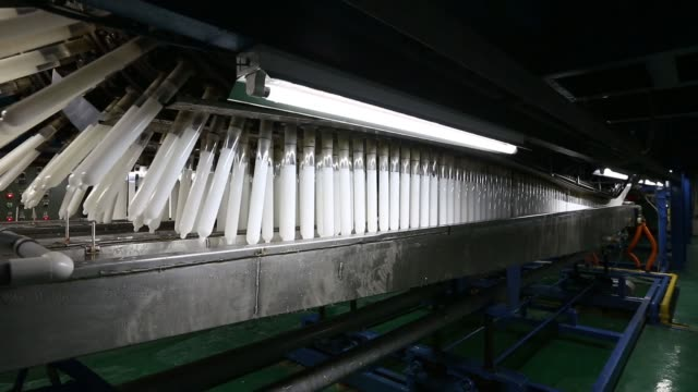 Various general views tubes move along an automated system as they are dipped into liquid latex to form condoms on the production line at the Unidus...