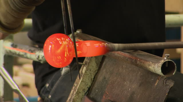 Various interior shots of glassblowing glass being made in workshop by anonymous glass blowers tool dipped into sand and heated in fire oven kiln to...