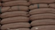 Various medium views of sacks of rice stacked inside a warehouse Wide exterior views of the entrance to Boonnapa rice mill in Chokchai A truck is...
