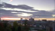 Various mid high rise city buildings various construction cranes in distance PAN to Millennium Stadium cloudy sky BG UK