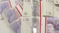 Various panning shots bundles of 20 pound sterling banknotes laid out on a worktop inside a Travelex store operated by Travelex Holdings Ltd in...