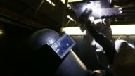 Various shots a bright light glows as an apprentice wearing a protective vizor welds a metal joint at Alstom SAs welding training facility in...