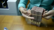 Various shots a clerk arranges bundles of Indonesian 100000 rupiah banknotes and 50000 rupiah banknotes on a desk at a currency exchange office in...