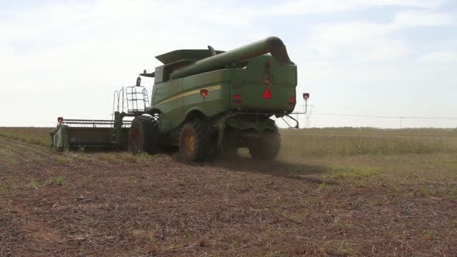 Various shots a John Deere S660 combine harvester manufactured by Deere Co harvests a crop of soybean plants in a field in Delmas South Africa on...