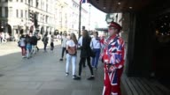 Various shots a man dressed in a Union Jack costume dances and welcomes customers outside a Cool Britannia souvenir stall in central London UK on...