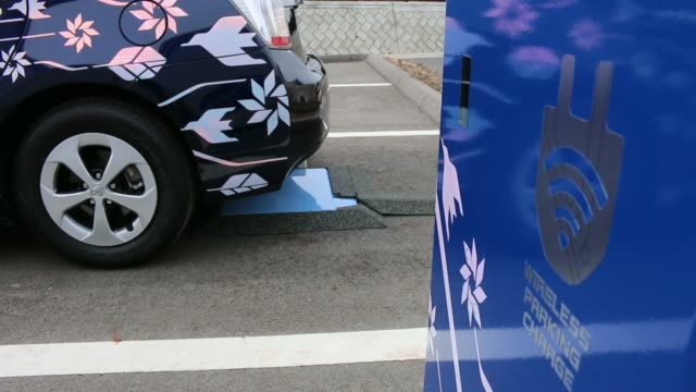 Various shots a Toyota Motor Corp Prius PHV plugin hybrid vehicle reverses to park over the company's wireless vehicle charging system which uses...