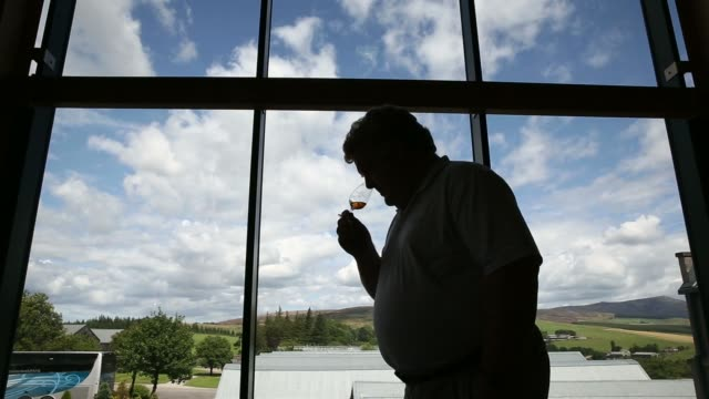 Various shots an employee samples a glass of The Glenlivet single malt whisky produced by Pernod Ricard SA at the companys distillery in...