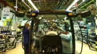 Various shots employees work on the cabs of Holland tractors on the production line at CNH Industrial NVs assembly plant in Basildon UK on Wednesday...