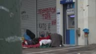 Various shots homeless Greek man lying asleep on pavement by ATM cashpoint and shuttered shops covered in graffiti people walking past Homeless in...