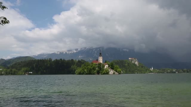 Various shots Lake Bled in the Julian Alps views of the Church of the Assumption on opposite bank mountains beyond Long shot man rowing a boat on...