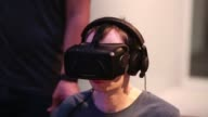Various shots male gamers wearing Oculus Virtual Reality Inc Rift Development Kit 2 headsets as they play 3D video games during the EGX gaming...