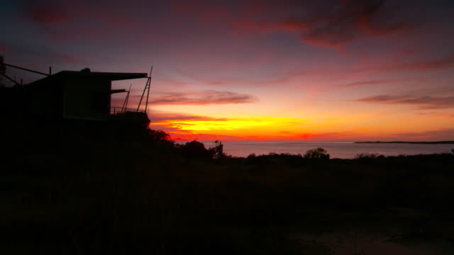 Various shots of a burnt orange sky at sunrise over the Timor Sea silhouette of cabins