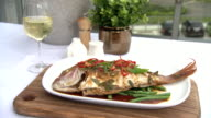 Various shots of a chilled glass of white wine accompanying a whole baked snapper with capsicum garnish sitting on sesame beans and sauce Salt and...