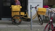 Various shots of a Deutsche Post postal worker riding a yellow bike along his delivery route in Berlin Germany A courier looks through a pile of mail...