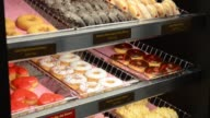 Various shots of a Dunkin Donuts Inc store in Manhattan New York US on Wednesday Feb 5 A tracking shot of the wall displaying all of the donuts A...