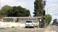 Various shots of a low income neighborhood in East Palo Alto California A wide shot of a small house at an intersection with a white SUV parked in...