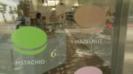 Various shots of a macaroon shop in Palo Alto California A medium shot through a colorful window of a macaroon shop A wide shot of the interior of a...