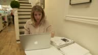 Various shots of a young blonde white female using a MacBook laptop in a cafe A wide shot of a young blonde white female using a MacBook laptop in a...