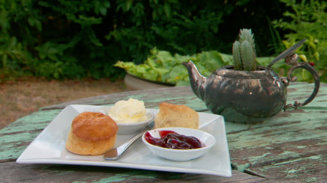Various shots of beautifully presented afternoon tea set on outdoor table fresh scones with strawberry jam and cream close up scones and strawberry...