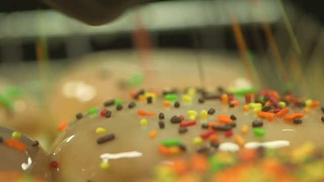 Various shots of Dunkin Donuts doughnuts being sprinkled at their headquarters in Canton Massachusetts on September 21 Tight shots of an employee...