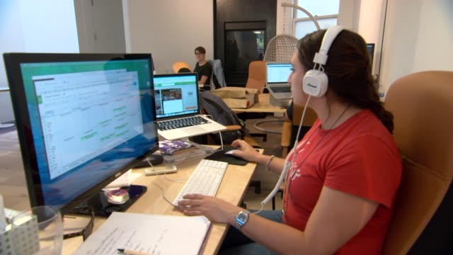 Various shots of female employees working at the modern Instacart offices in San Francisco California A medium shot of a young white female employee...