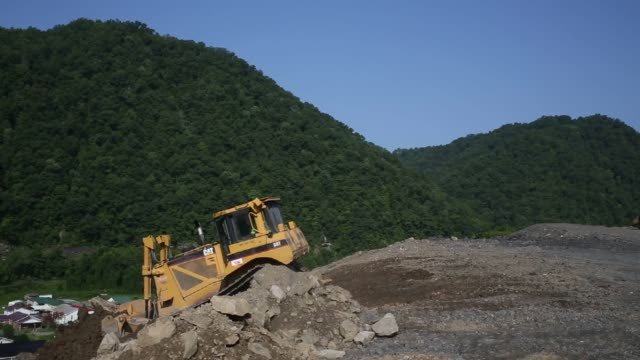Various shots of heavy machinery at a construction site for Highway 460 in Elkhorn City Kentucky Wide shots of a CAT bulldozer pushing dirt and rock...