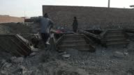 Various shots of laborers building forms for concrete blastwalls in Kabul Afghanistan on Monday April 14 A wide shot of two workers constructing a...