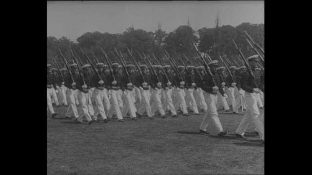 Various shots of marching naval cadets in a field coming to attention / honor guard marches to center where officers and a woman wearing hat and...