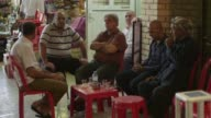 Various shots of people going about their daily lives in Erbil Iraq Shots of people seated at tables drinking at the Qaysari Bazaar Close up shot of...