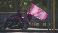 Various shots of pink toy animals sitting on motor bikes decorated in pink feather boas and ribbons Riders wearing various pink themed outfits / pink...
