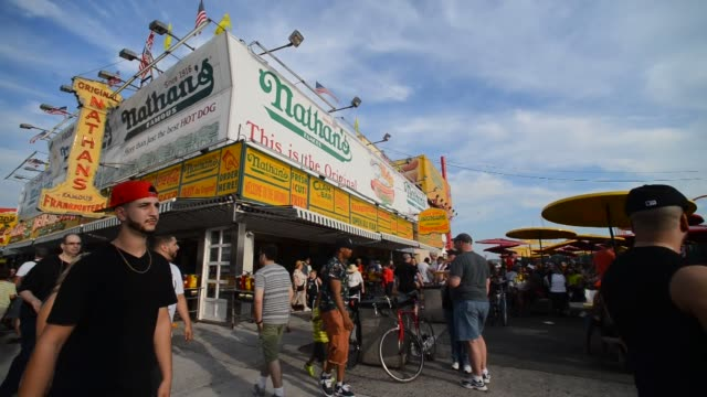 Various shots of the original Nathans Famous hot dog shop in Coney Island New York A wide shot of Nathans Famous hot dog shop as people pass by Wide...