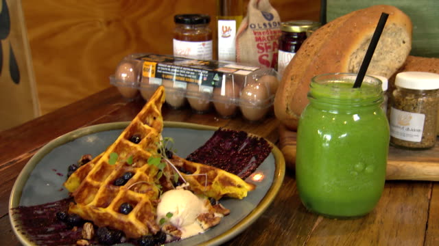 Various shots of waffles with blueberries and ice cream accompanied by a green smoothie in jar glass with straw Carton off eggs spices and loaf of...