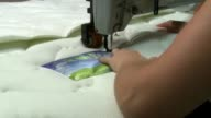 Various shots of workers inside the Polyron Factory in Ashkelon Israel just north of Gaza Workers use sewing machines to add stitches to reems of...