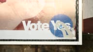 Various shots pedestrians and vehicles pass a vandalized pro independence yes campaign billboard advertisement in Edinburgh UK on Tuesday Sept 16 Low...