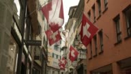 Various shots pedestrians pass beneath national flags of Switzerland as they fly on a retail street in Zurich Switzerland on Monday July 21 Tilt down...