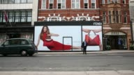 Various shots pedestrians walk past a hoarding outside the construction site of a new Fendi store a luxury unit of LVMH Moet Hennessy Louis Vuitton...