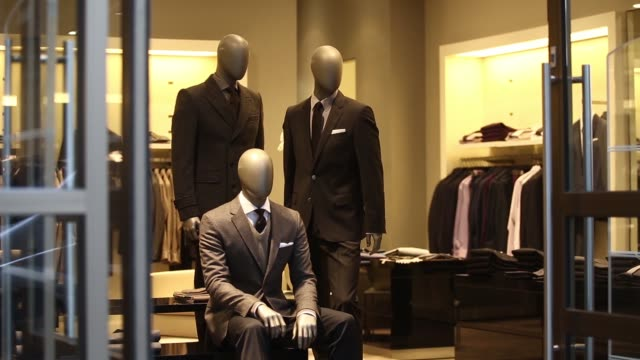 Various shots pedestrians walk past a Hugo Boss AG luxury clothes store in London U K on Monday Nov 3 Mens suits are displayed on mannequins in...