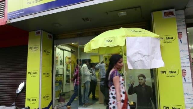 Various shots pedestrians walk past an Idea Cellular Ltd retail store in Mumbai India on Wednesday Jan 29 Idea information pamphlets are laid out on...