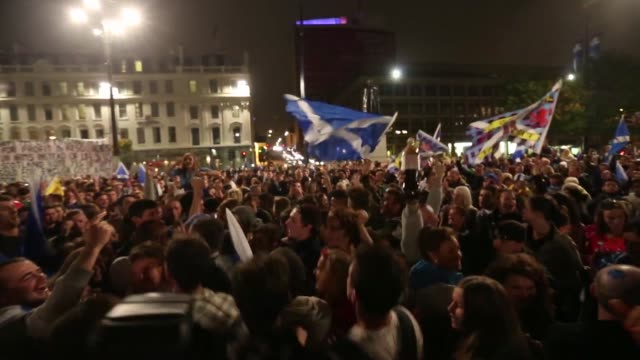 Various shots pro independence yes campaign supporters wave St Andrews or Saltire flags the national flag of Scotland cheer and chant during a night...