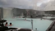 Various shots tourists bathe in the Blue Lagoon geothermal spa as steam rises in Grindavik Iceland on Friday Nov 8 High angle views visitors pass...