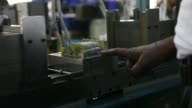 Various shots workers manually fill the cores of transformers on the transformer line at the Su Kam Power Systems Ltd power inverter factory in...