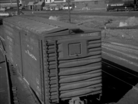 Various switchmen including Warren Scott signaling freight cars being bumped on railroad tracks coupling unhinging freights moving open freight car...