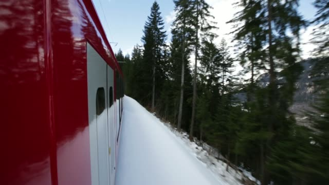 Various views from a moving Rhaetian Railway train as it travels along the tracks through the snow and mountains towards Davos Switzerland on Sunday...