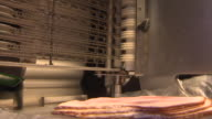 Various views of ham coming out of a meat slicer at a butchers