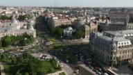 Various wide high angle skyline views automobile traffic moves along the road towards the University roundabout in the center of Bucharest Romania on...