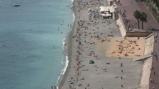 Various wide high angle views holidaymakers on the beach and promenade along the Mediterranean Sea coastline in Nice France on Friday Sept 26 Pan L R...