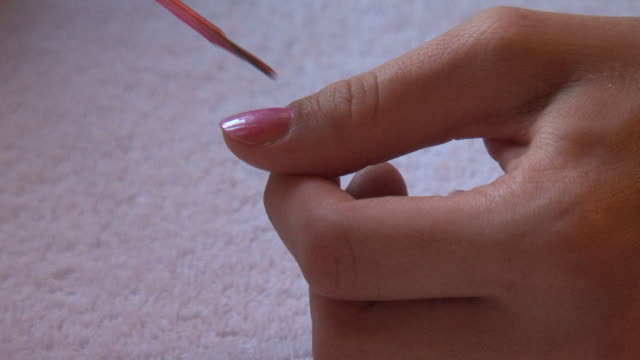 Varnishing the fingers in pink