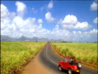 Vast plantation fields with bright blue sky and white fluffy clouds above mountains in the background red jeep drives along road away from camera Mauritius