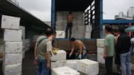 Vegetable wholesalers unload boxes of produce from trucks at the Cheung Sha Wan Wholesale Vegetable Market in Hong Kong Vegetable wholesalers handle...